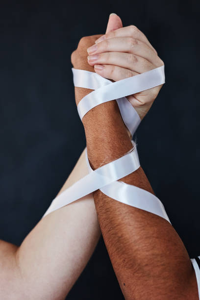 I'm only free when we're all free Studio shot of two unrecognisable women bound together, holding their hands in solidarity against a dark background anonymous activist network stock pictures, royalty-free photos & images