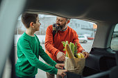 Photo of father and son packed groceries after shopping in the trunk