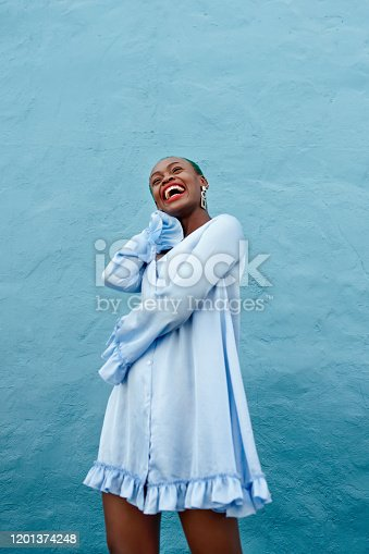 Cropped shot of a cheerful young woman posing while standing against a blue background outside during the day