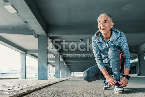 Running shoes - closeup of mature, gray hair woman tying shoe laces and looking forward. Female sport fitness runner getting ready for jogging outdoors  in spring. Senior fitness woman getting ready to start running workout during the sunny day. Fit and sporty short hair woman tying her laces before a run.