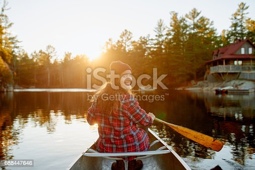 Shot of a young woman enjoying a day at the lake with her rowing boat
