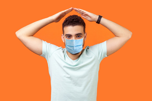 istock I'm safe. Portrait of cheerful brunette man with medical mask in casual white t-shirt standing with hands over head, making roof gesture. 1214079095