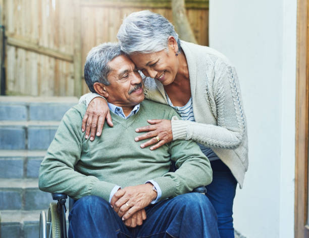 I'm so blessed to have you in my life Shot of a cheerful elderly man seated in a wheelchair while being held by his loving wife outside at home during the day husband stock pictures, royalty-free photos & images