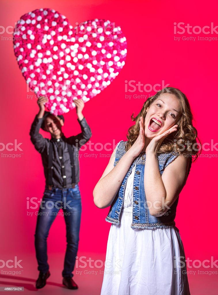 Surprised beautiful girl is standing on pink background. Her cute...