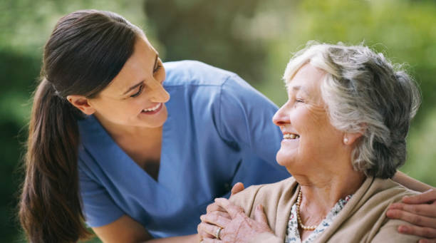 I'm so happy to see you happy Shot of a senior woman in a wheelchair being cared for a nurse patience stock pictures, royalty-free photos & images