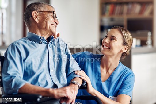 Shot of a senior man in a wheelchair being cared for by a nurse at home