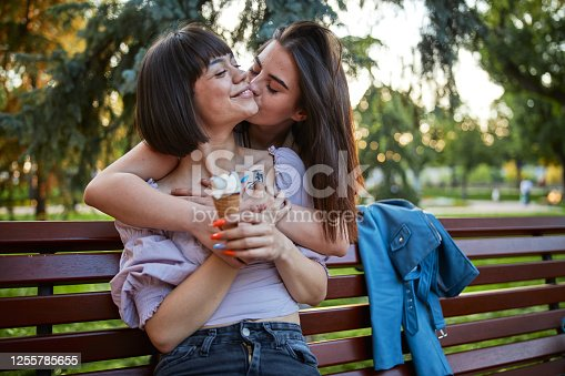 Happy woman hugging her girlfriend from behind while she sitting on the park bench and eating ice cream