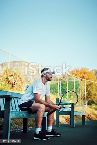 Shot of a sporty young man sitting on a bench on a tennis court