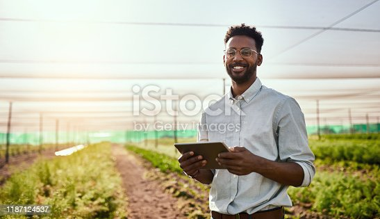 Cropped portrait of a handsome young male farmer using a tablet while working on his farm