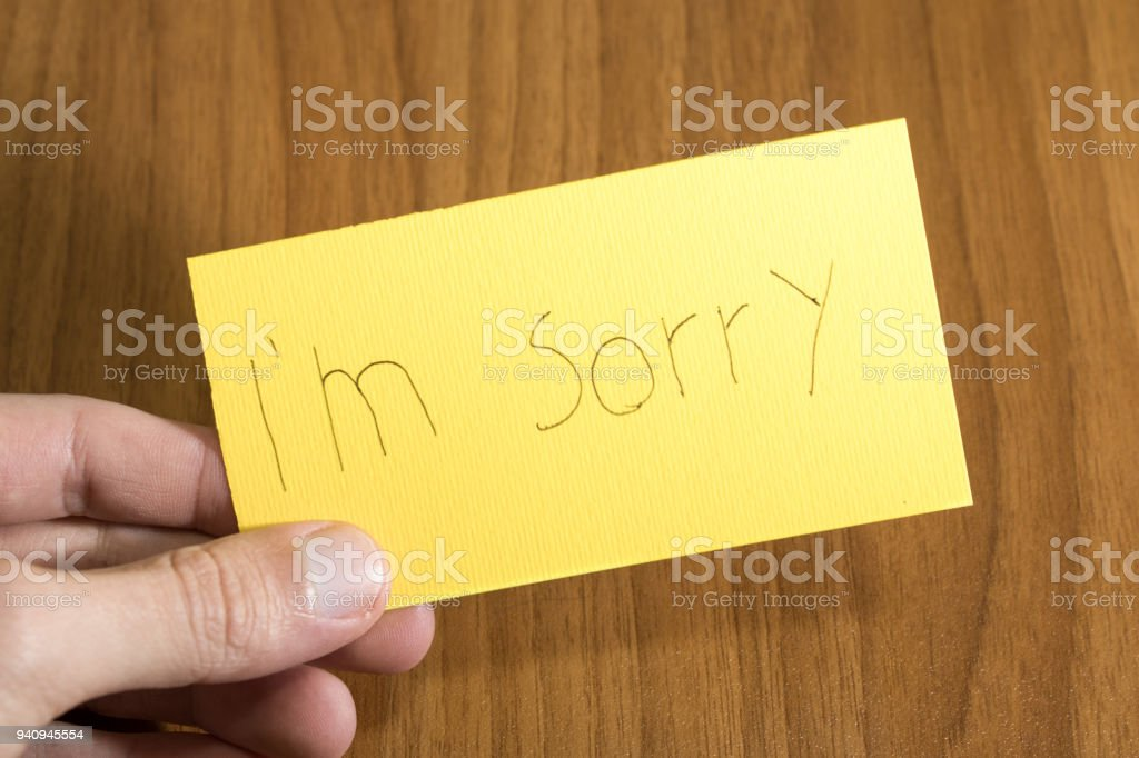 I'm sorry handwrite on a yellow paper with a pen on a table composition stock photo