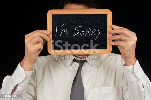 homme non-reconnaissable se cachant derrière une ardoise d'école sur laquelle est écrit en anglais je suis désolé