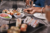 Cropped shot of an unrecognizable person eating sushi at a restaurant