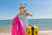 Excited little 4 year old girl on a beach wearing scuba mask and inflatable ring, while holding suitcase