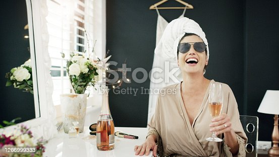 Cropped shot of a woman having champagne while getting ready on her wedding day