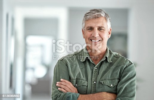 Portrait of a mature man standing with his arms crossed at home