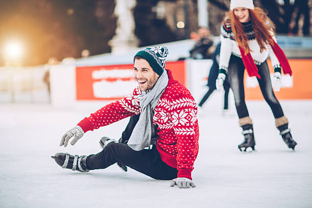 I'm still learning how to skating on ice Friends having so much fun while ice skating.  Wearing warm clothing. City is decorated with christmas lights. ice skating stock pictures, royalty-free photos & images