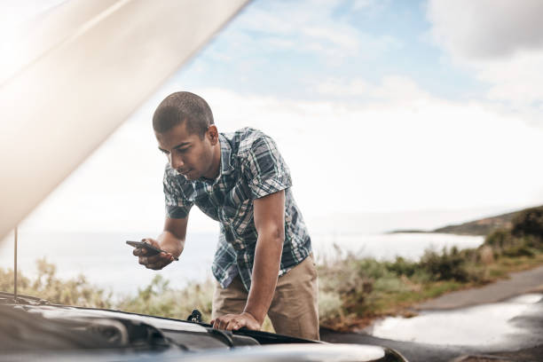 I'm stuck in the middle of nowhere, I need assistance Cropped shot of a young man with his broken down car on the side of a road aground stock pictures, royalty-free photos & images