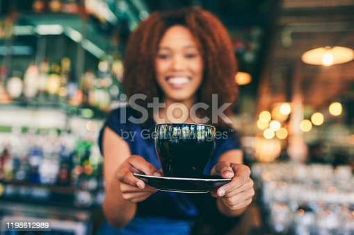 Cropped shot of a young woman serving a cup of coffee in a cafe