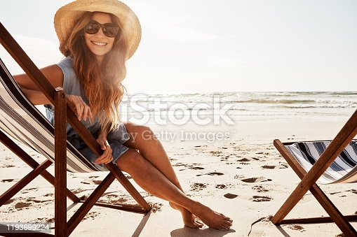 Portrait of a young woman relaxing on a lounger at the beach