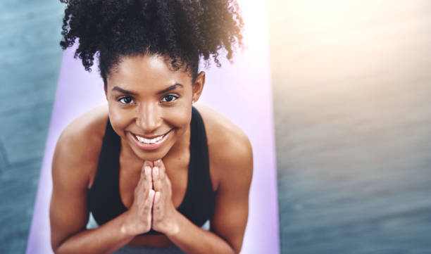 I'm thankful for yoga Shot of a beautiful young woman practising yoga in a studio prayer pose yoga stock pictures, royalty-free photos & images