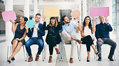 Shot of a group of businesspeople holding colorful speech bubbles while waiting in line in a modern office