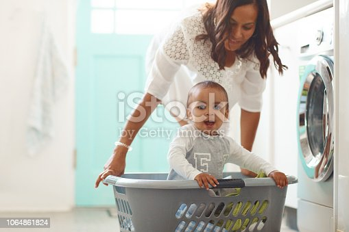 Shot of a mother and her adorable baby boy doing the laundry at home