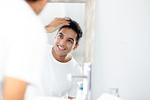 Cropped shot of a young man touching his hair while looking into the mirror