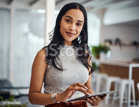 Portrait of a young businesswoman using a digital tablet in an office