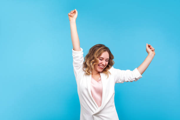 I'm winner! Portrait of ecstatic overjoyed lady dancing with raised arms, smiling excitedly. blue background stock photo