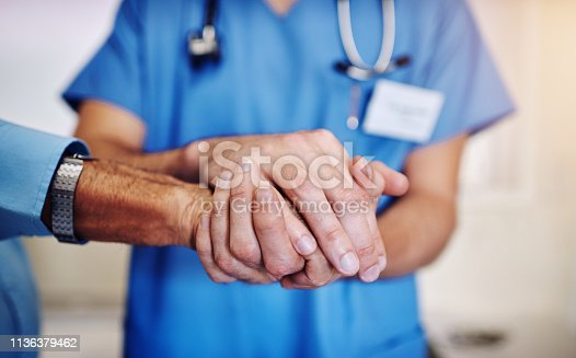 Shot of an unidentifiable young doctor holding his senior patient's hand in support