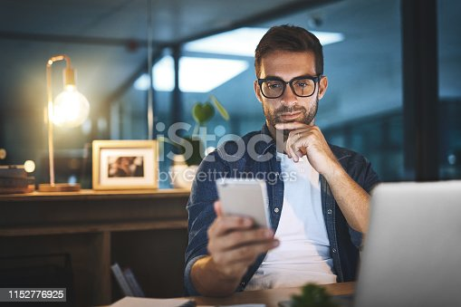 Shot of a handsome young businessman using his cellphone while sitting at his desk in a modern office