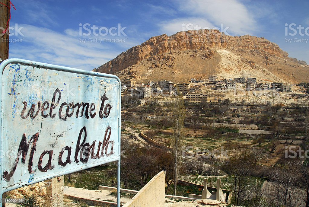 Maaloula / Maalula, Syria: welcome sign, houses under the cliff royalty-free stock photo