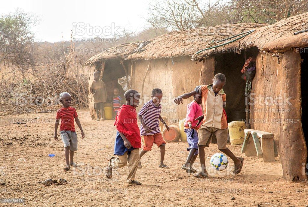 Maasai boys playing football (soccer) in Kenya village, Africa stock photo