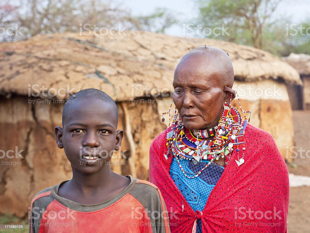 Maasai grandmother with her grandson outside a dung hut stock photo