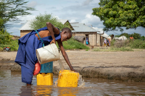 maasai woman with water containers to collect drinking water stock photo
