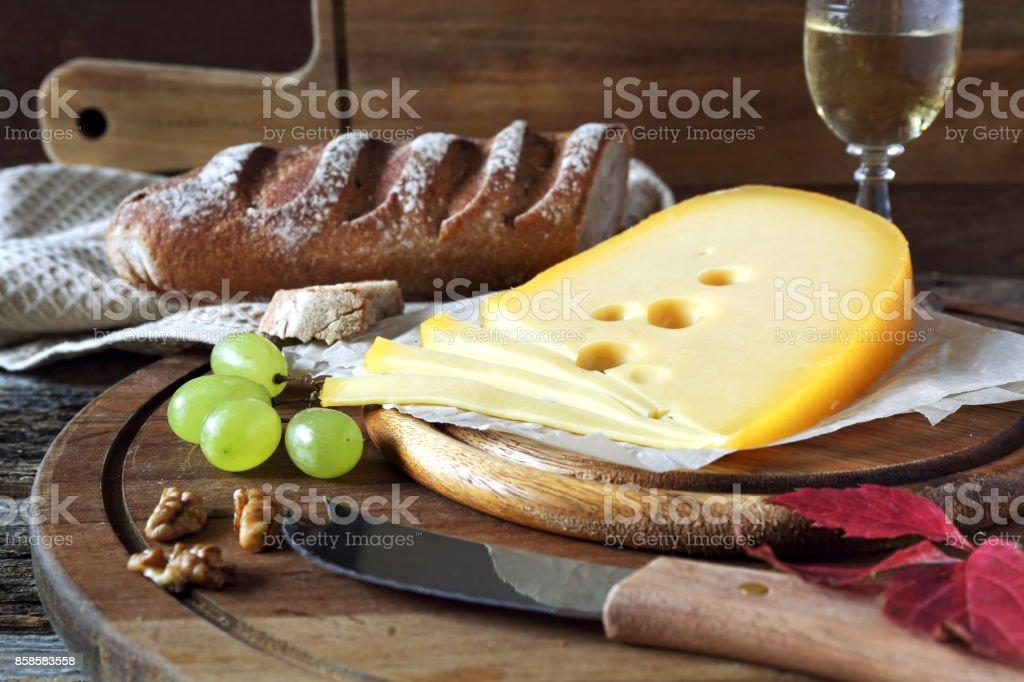 Maasdam cheese, bread and glass of white wine stock photo