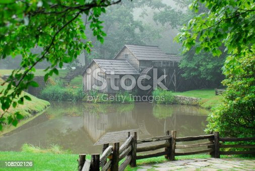 An historic grist and lumber mill located on the Blue Ridge Parkway sits alongside a pond enshrouded by fog on a late afternoon day.