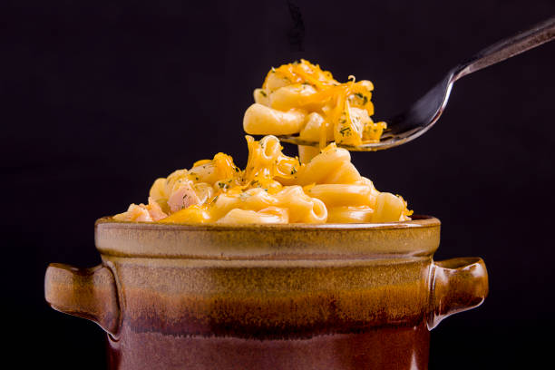 Mac and cheese on a fork over the bowl. stock photo