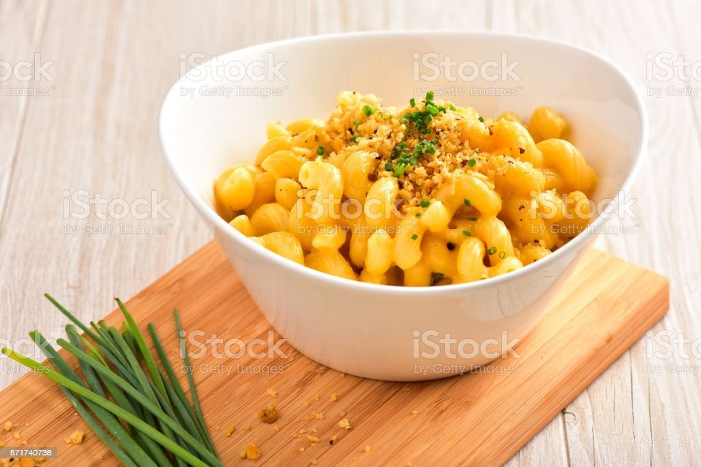 Mac and Cheese on Small Wood Board Garnished with Chives and Breadcrumbs stock photo