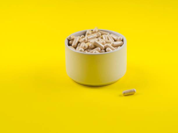 Maca powder in capsules on yellow background stock photo