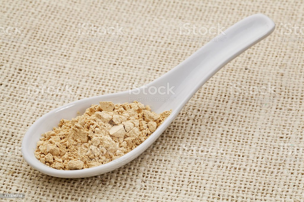 maca root powder on a ceramic spoon royalty-free stock photo