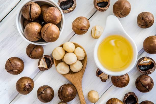 Macadamia-Nussöl und geschälte Macadamia-Nuss auf weißen Tisch, verwenden Sie für gesunde Haut und Haare und natürliche Heilung Ölbehandlung, Overhead und Draufsicht – Foto