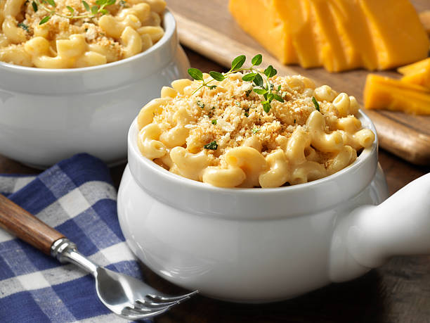 Macaroni and cheese in a white bowl on blue plaid tablecloth Comfort food. Kids meal. Two single serving casseroles with creamy macaroni and cheese with an herb bread crumb topping. Large block of cheddar cheese in background. Focus on top of first casserole. H4D-40 with shift adapter. See other Mac and Cheese dishes in my Pasta Lightbox. burwellphotography stock pictures, royalty-free photos & images