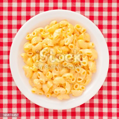 Top view of white dish full of macaroni and cheese over checked tablecloth