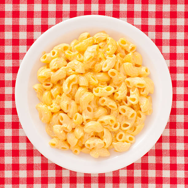 Macaroni and cheese Top view of white dish full of macaroni and cheese over checked tablecloth macaroni stock pictures, royalty-free photos & images