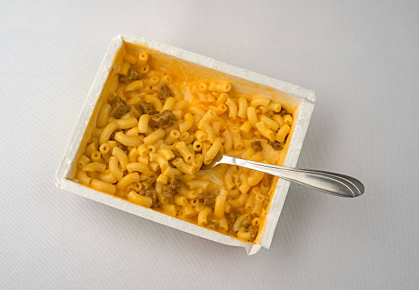 macaroni and cheese with burger plus fork on table - hamburger makkaroni stock-fotos und bilder