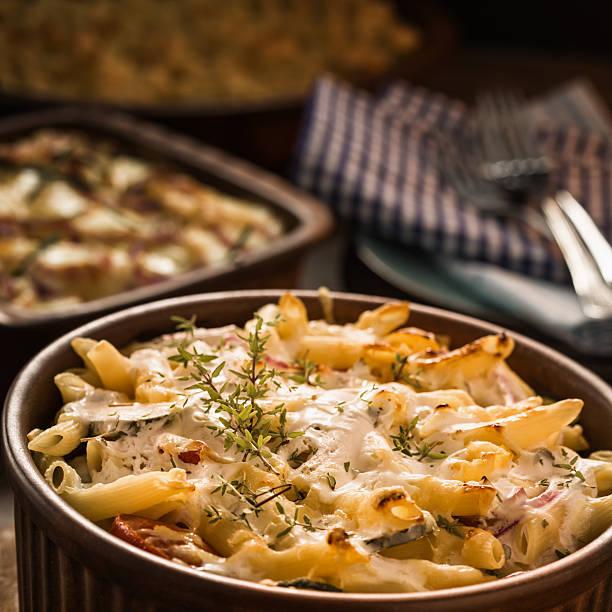 makkaroni-gratin - käse zucchini backen stock-fotos und bilder