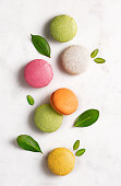 Macarons flat lay with leaves on marble background. Top view