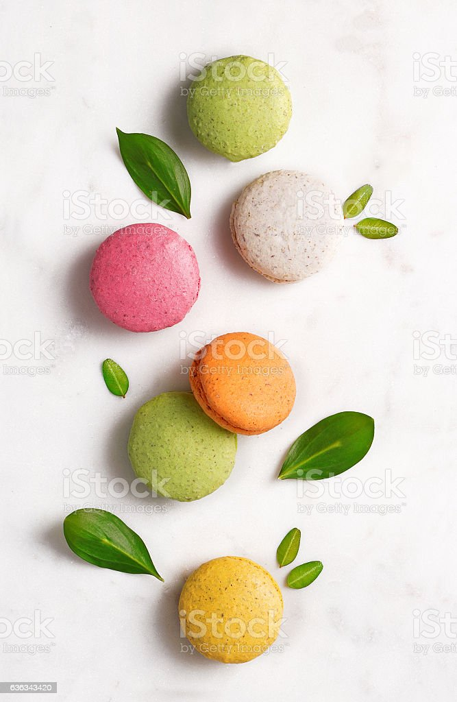 Macarons flat lay with leaves on marble background. Top view stock photo