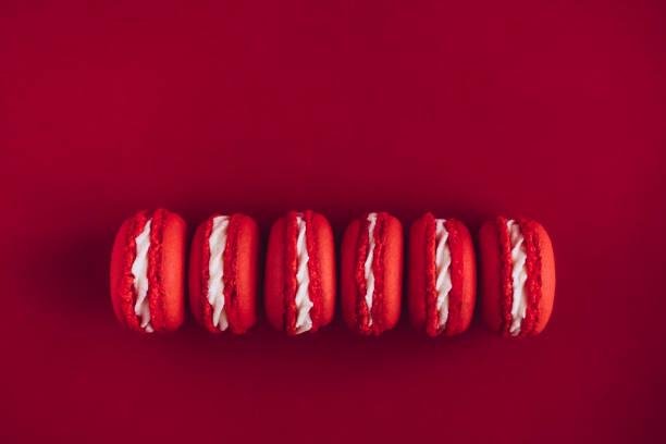 macarons auf gleichen farbigen hintergrund - modetorten stock-fotos und bilder